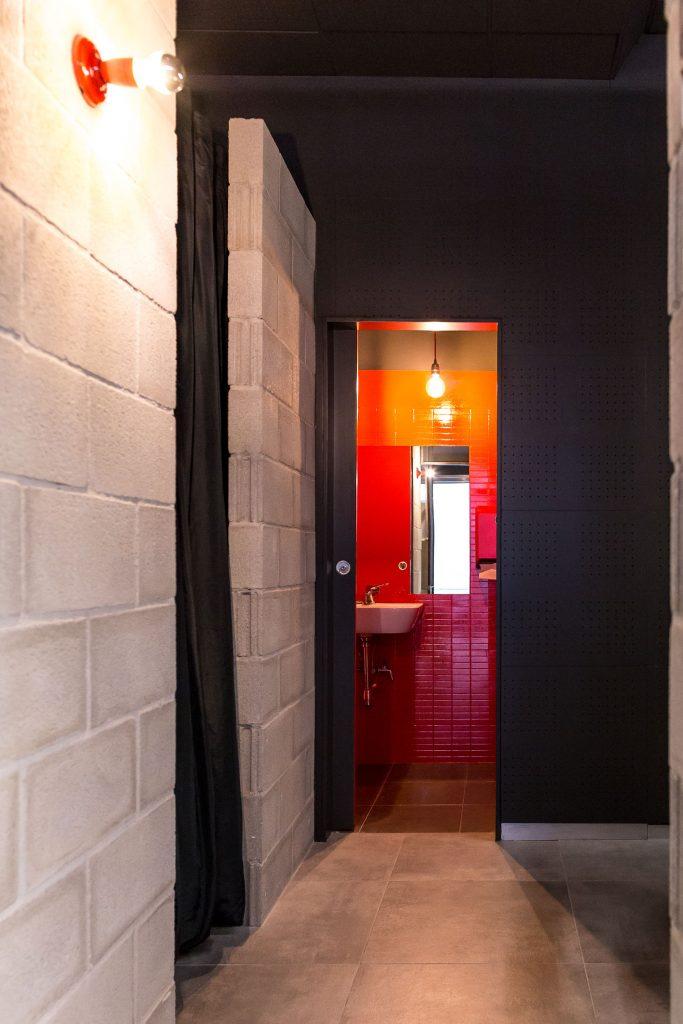 Interior muros hormigón y acceso al baño rojo