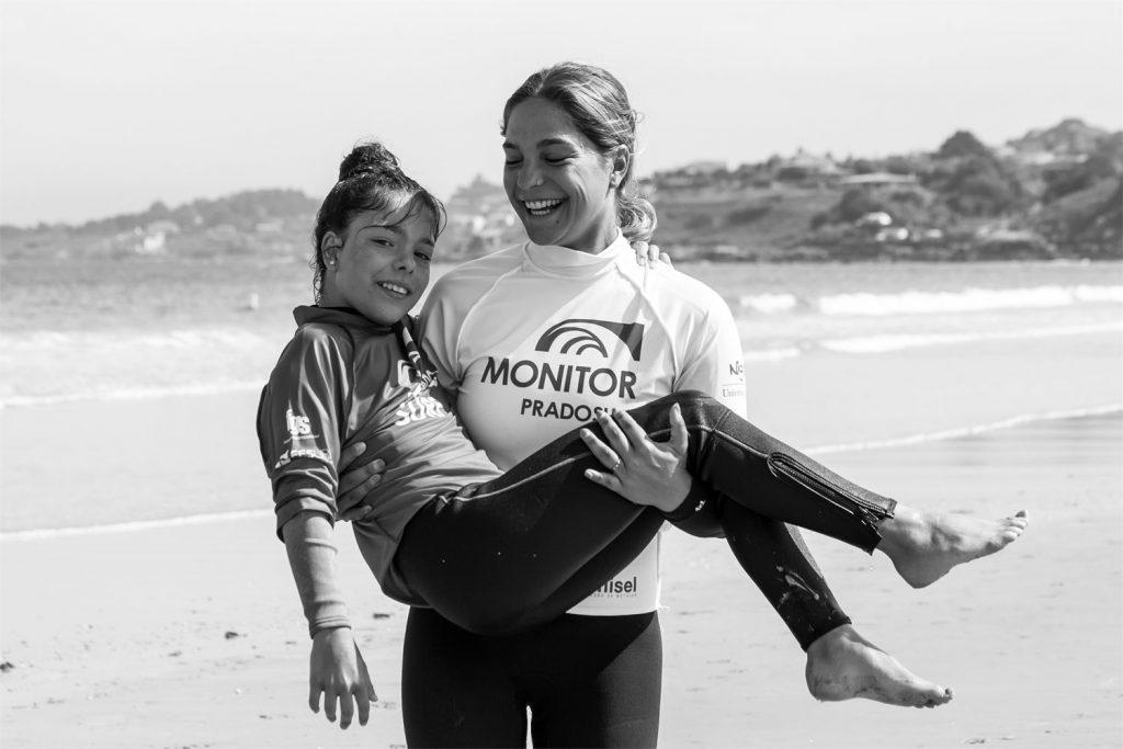 Monitora de surf y niña en brazos