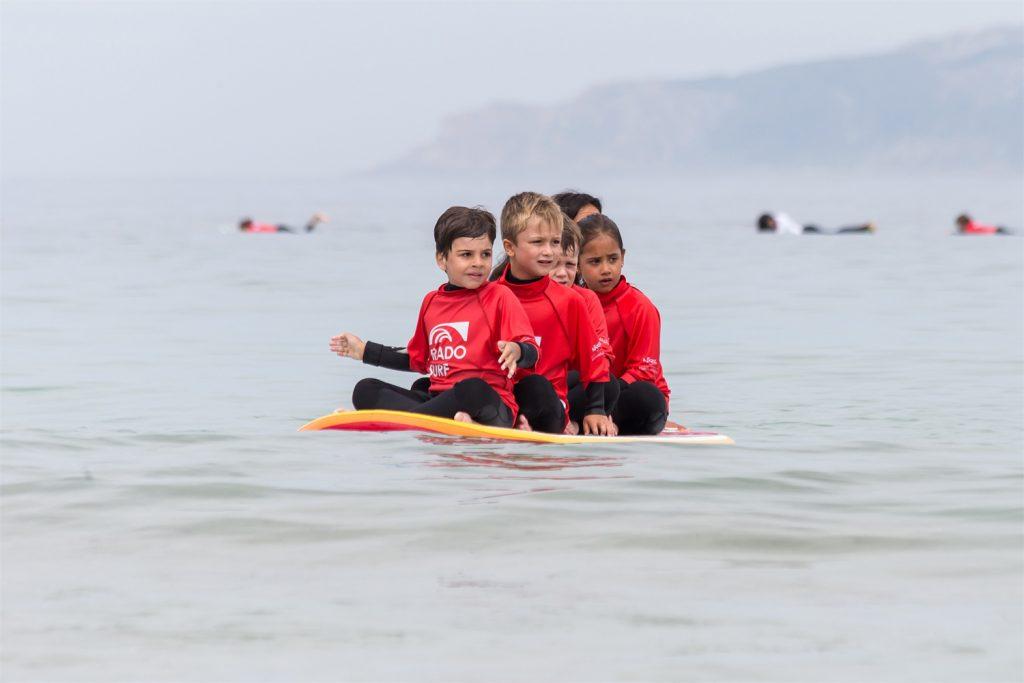 Grupo de niños surfeando sobre una misma tabla