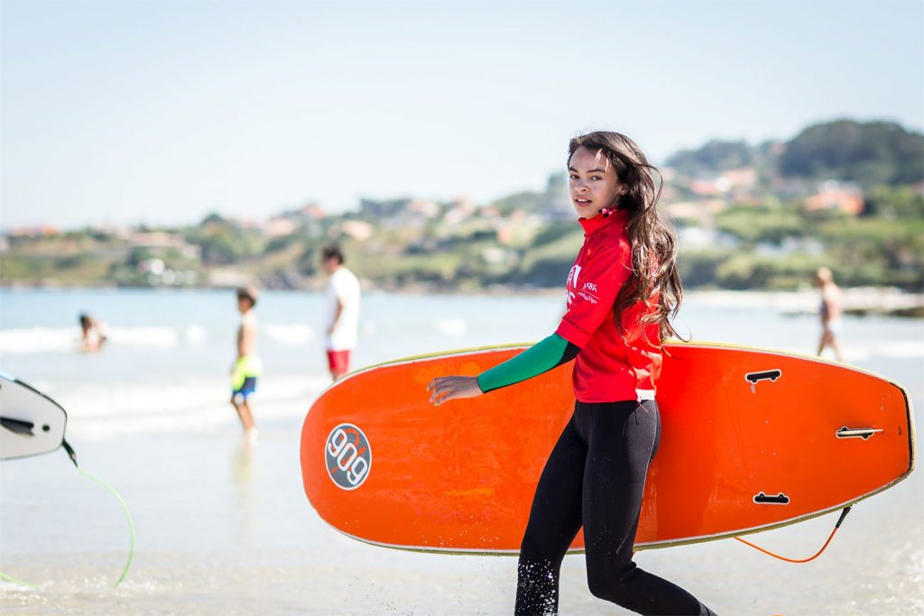 Chica surf acercándose al agua en Nigrán