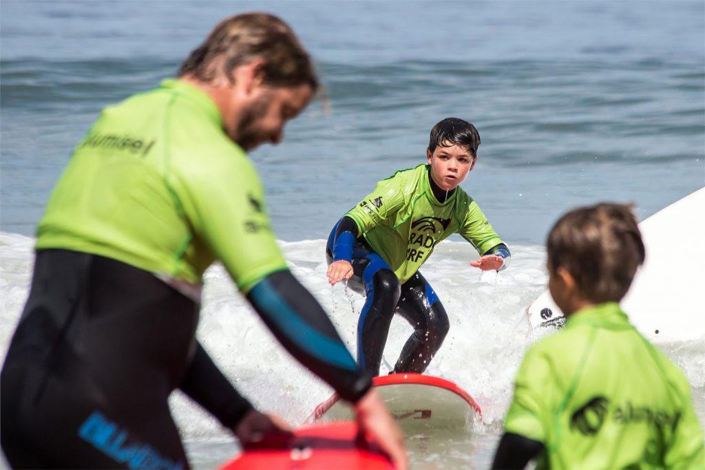 Niño pequeño aprendiendo a surfear
