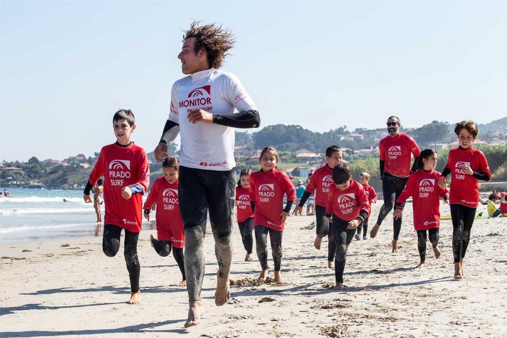 Niños y monitor de surf corriendo por la arena