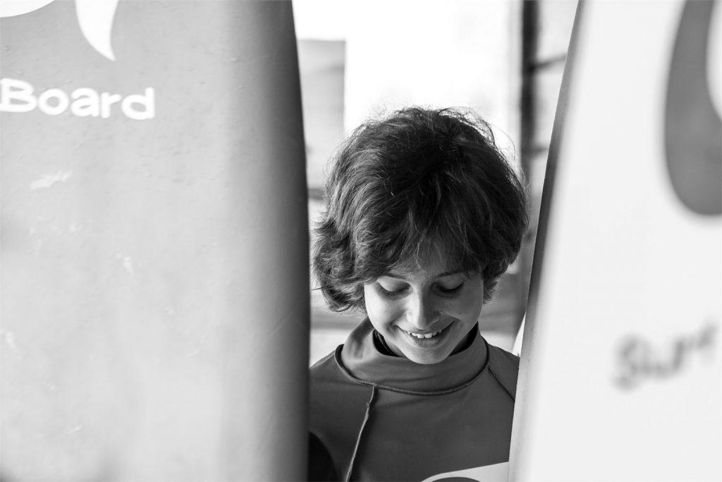 Retrato niño entre tablas de surf