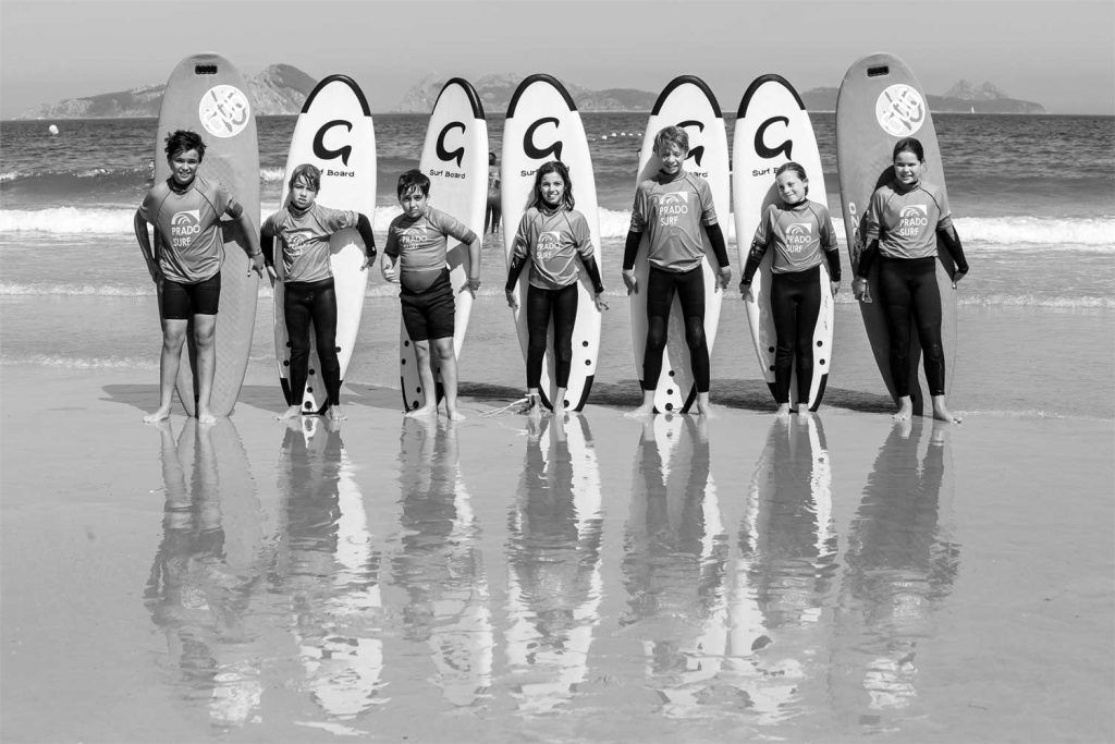 Grupo de niños posando con las tablas de surf